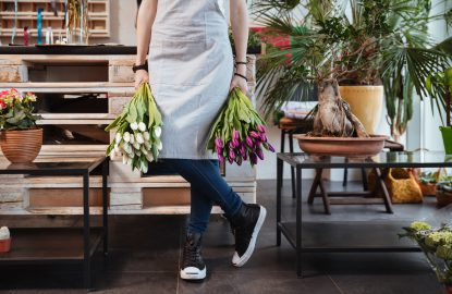Closeup of young woman florist in apron and sneakers with two bouquets of tulips standing in flower shop
